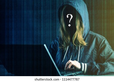 Anonymous girl hacker programmer uses a laptop to hack the system. Stealing personal data. Creation and infection of malicious virus. The concept of cyber crime and hacking electronic devices