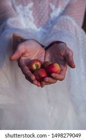 Anonymous girl with white dress holding apple in her hands
