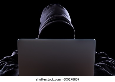 Anonymous hacker with laptop in the dark. Cyber security concept