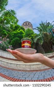 Anonymous hand servicing Turkish Tea Near the Galata Tower