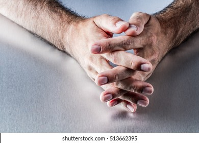 anonymous male hairy hands crossing fingers together waiting or thinking, explaining and communicating about moderation or patience in body language