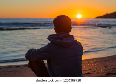 Anonymous man enjoying dramatic sunset on a beach. Enjoy life at peaceful evening hour. Feel yourself through nature.