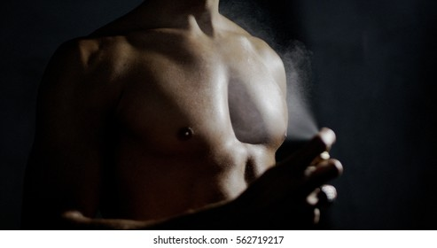 anonymous man spraying fragrance in extreme slow motion, with scent particles to wet skin after showering.