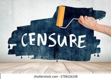 Anonymous man's hand painting grungy wall black with paintroller, big white title 'CENSURE' appearing on black painted spot. Strong criticism. Debatable issues. Restricted action.