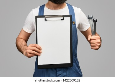 Anonymous mechanic holding two spanners and demonstrating empty work plan against gray background