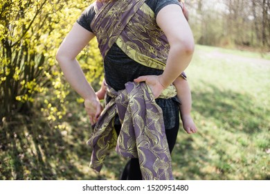 Anonymous mother wrapping a shawl sling behind her back carrying her baby in front. Modern babywearing.