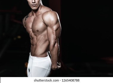anonymous muscular athletic bodybuilder fitness man model with big muscles showing triceps muscle in the gym