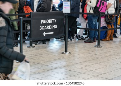 Anonymous passengers in queue behind PRIORITY BOARDING sign at the airport. All brands/logos removed