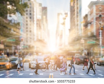 Anonymous people crossing street in Manhattan New York City with sunlight in background