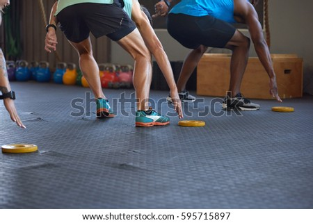 Anonymous people reaching lunging in gym as they run fast short sprints in gym