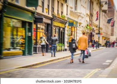 Anonymous people walking down high street holding shopping bags