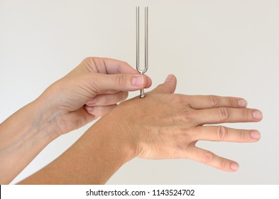 Anonymous person holding metal tuning fork against hand for therapy over white background. Includes copy space.