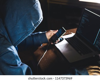 anonymous person in the hood sitting in front of computer working with laptop and mobile phone