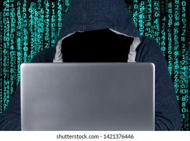 Anonymous person in hooded sweatshirt sitting in front of computer. Hacker works with laptop and tries to decrypt password.Hacker working on computer. He has numbers and a binary system around him.
