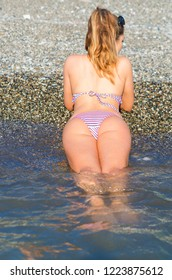 Anonymous sexy girl in a bikini lying on her belly. Female butt on a pebble beach. Sunny day on a seaside.