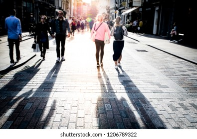 Anonymous shoppers on high street- in to the sun with long shadows