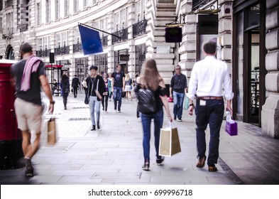 Anonymous shoppers walking down busy London shopping street