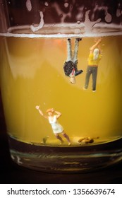 Anonymous, unrecognizable miniature people in a glass of beer. Binge drinking concept. Tiny people with a drinking problem at a crazy party. Last call, or time to seek help with a drinking problem.