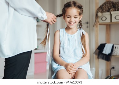Anonymous woman braiding hair of little wonderful girl keeping eyes closed and smiling happily.