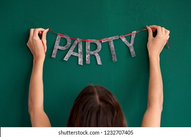anonymous woman hands setting up for party, hanging up glittery sparkly message bunting for festive celebration
