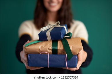 anonymous woman holding homewrapped presents to the camera, creative DIY gift wrap birthday christmas celebration