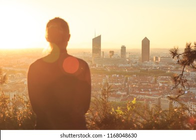 Anonymous woman looking at the skyline of Lyon during sunrise. Focus on skyline.