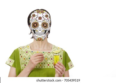 Anonymous woman in traditional clothing wearing skull mask Catrina celebrating Day of the Dead.