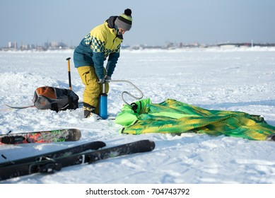 Anonymous woman in warm clothing pumping colorful parachute for snowkiting in snowy field.