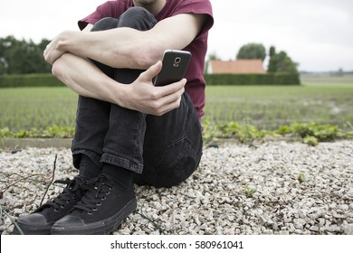 An anonymous young man sitting in front of a green field, holding his legs and a mobile phone. A concept about online bullying, quarter life crisis, depression, loneliness and emotional health issues.