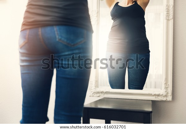 anorexia concept - woman looks at her fat reflection in mirror