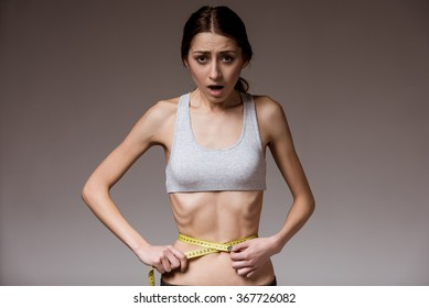 Anorexia. Thin girl shows her narrow waist with a tape measure in hand