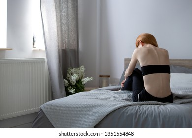Anorexic woman sitting on a bed in a bedroom