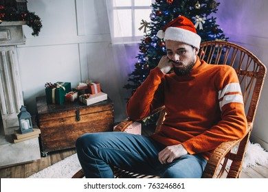Another close up of unhappy and sad man sitting in the brown rocking chair and thinking about something. He is prepared for Christmas party but the man doesn' have a good mood at all. He hopes it will