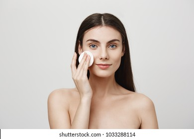 Another day of fighting for beauty. Indoor shot of beautiful young european woman taking off makeup with cotton pad, smiling and looking at camera like in mirror, standing over gray background
