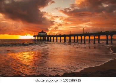 Another gorgeous California orange and red sunset over the Pacific Ocean on the beach next to the Manhattan Beach Pier near Los Angeles, California.