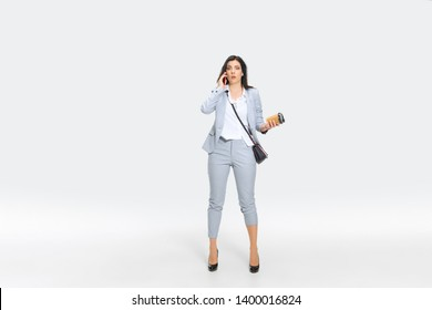 Another minute and you're fired. Young woman in gray suit is getting shocking news from boss or colleagues. Looking numbed while dropping coffee. Concept of office worker's troubles, business, stress.