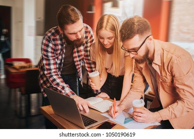 Another picture of three business partners working on project. They have the meeting in cafe. Guys and girl studying grapics and writiing down the information about that.