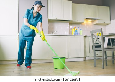 Another picture of young female cleaner works in kitchen. She washes floor with mop. Green bucket stands besides her. Girl is calm and peaceful.
