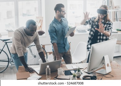 Another reality is here! Group of young business people working and communicating together while one of them wearing VR headset in creative office