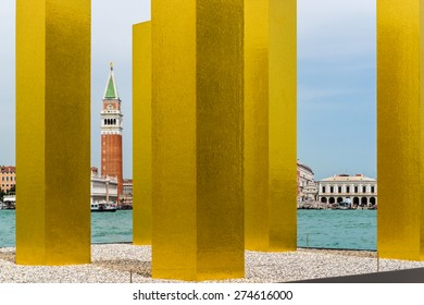 Another view to St. Mark's Square of Venice through recently erected, modern, golden-shimmering pillars representing modern arts.