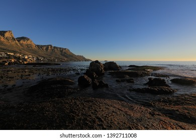 Another view at the Twelve Apostles from the rocks in the cold Atlantic Ocean at Camp's Bay in South Africa. Camp's Bay is bathing in the last rays of the setting sun.