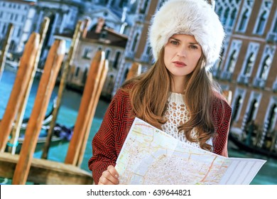 Another world vacation. Portrait of modern woman on embankment in Venice, Italy in the winter with map