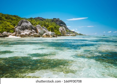Anse Source d'Argent - Paradise like tropical beach. Shallow lagoon in low tide time, Granite boulders and palm trees. La Digue island, Seychelles