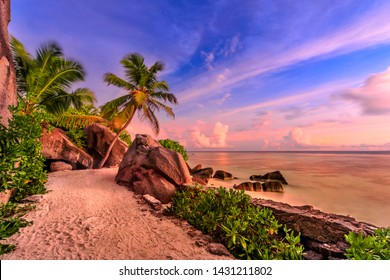 Anse Source d'Argent in Seychelles, La Digue with dramatic colorful sky at eveing. Shaped rock stone of granite, palm trees and seashore. Source d'Argent Beach paradise of Seychelles. Long exposition.