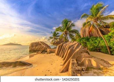 Anse Source d'Argent at sunset. Seychelles, La Digue. Landscape of palm trees and rock stone of granite blouders. Sunlight over the horizon. Source d'Argent Beach is paradise of Seychelles Islands.