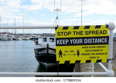 Anstruther, Fife, Scotland/ United Kingdom - 18 July 2020 : A sign in the fishing village of Anstruther promoting social distancing during the Covid-19 coronavirus pandemic