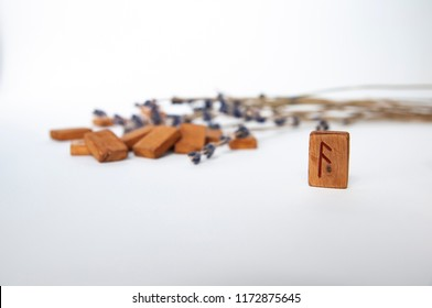 Ansuz. Scandinavian runes. Wooden runes on a table on a white background.