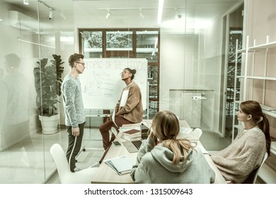 Answering near whiteboard. Blonde student wearing glasses feeling uncomfortable answering near whiteboard