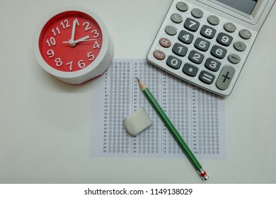 Answers sheet with green sharp pencil, clock, calculator and rubber isolated on white background. Top view of them. Take the exam timely concept.