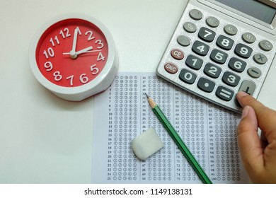 Answers sheet with green sharp pencil, red clock, finger on calculator and rubber isolated on white background. Top view of them. Take the exam timely concept.